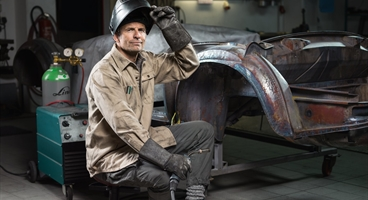 Hobbyist: Man welding and maintaining his classic car.  The image is only allowed to be used for campaigns targeting the Small & Medium Enterprise (SME) segment.